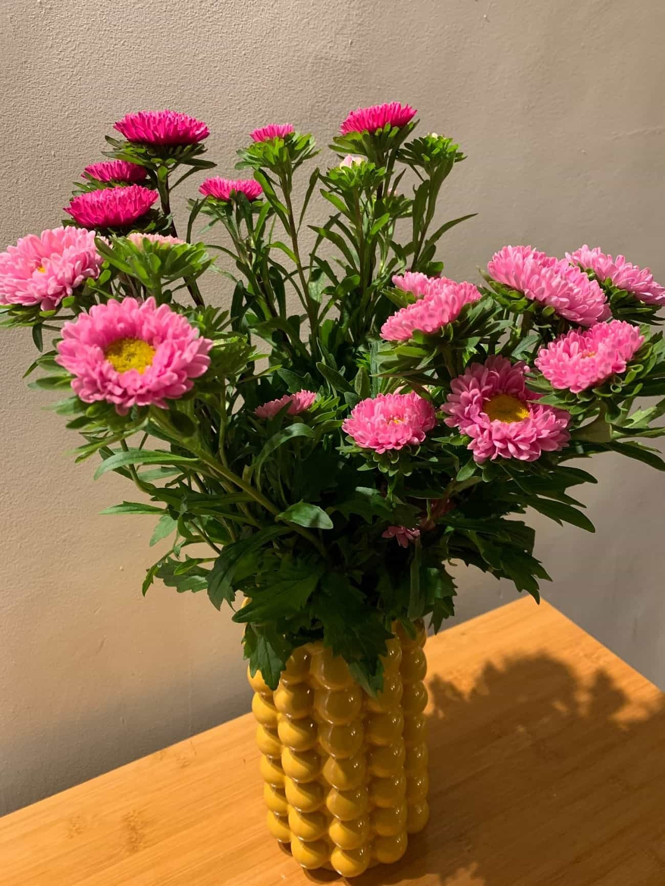 Bright flowers in a yellow vase