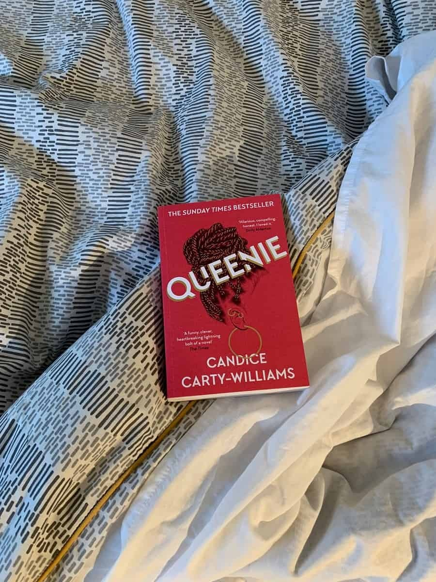 Reading Queenie in an unmade bed
