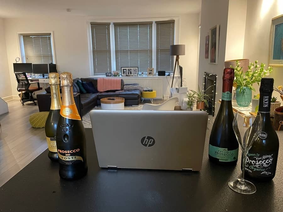 Four Prosecco bottles next to a laptop
