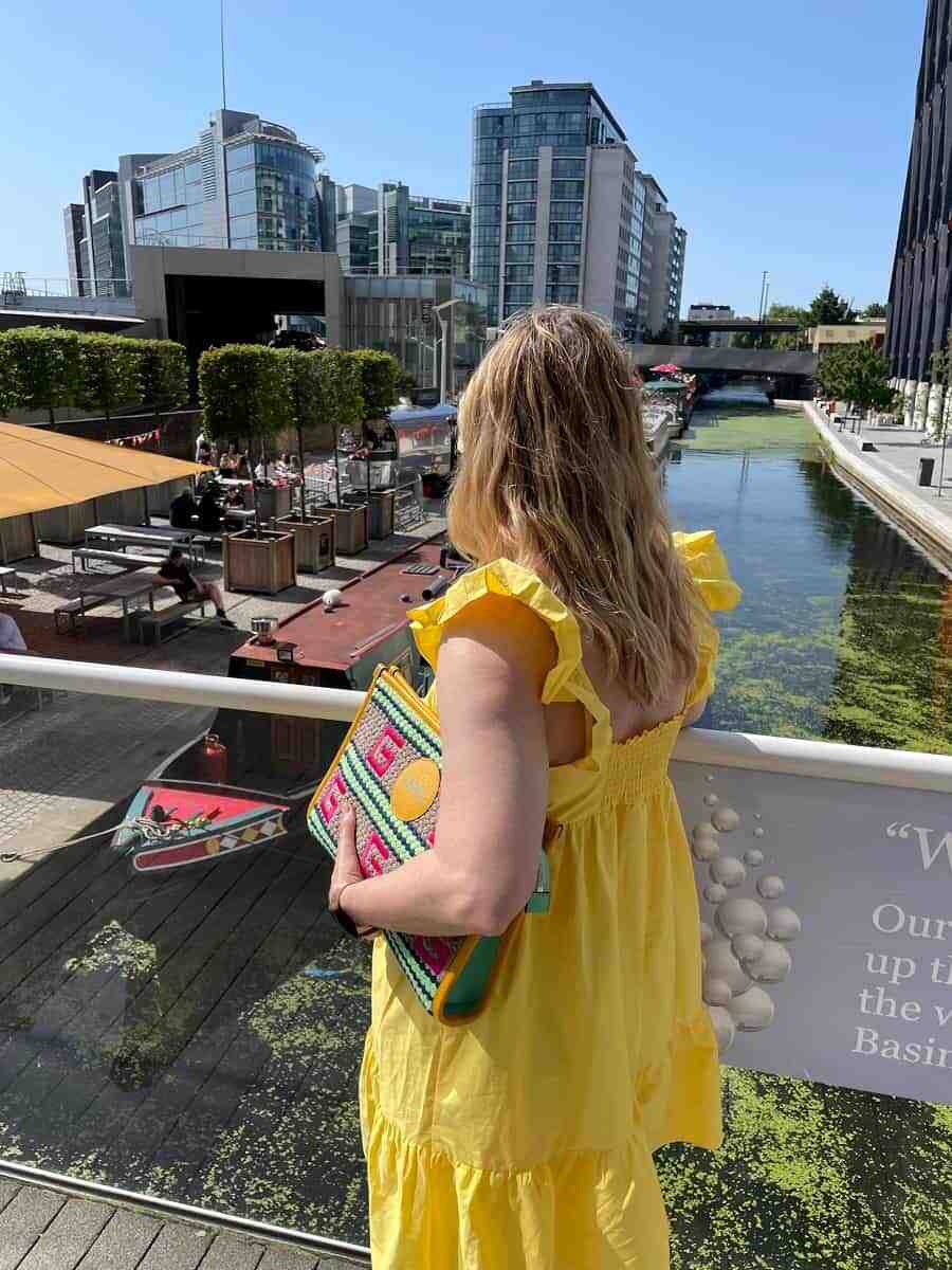 Kirsty is wearing a bright yellow dress and looking over the canal in Paddington