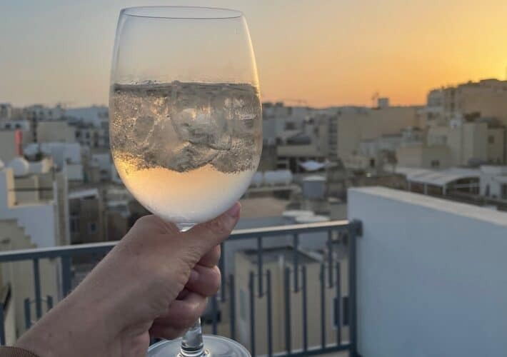 Hand holding a wine glass with a sunset in the background